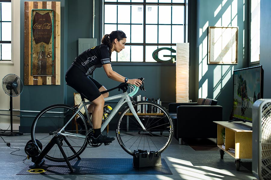 Female cyclist riding on indoor bike trainer