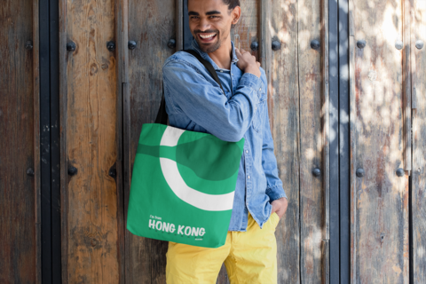 tote-bag-mockup-featuring-a-smiling-man-standing-by-a-wooden-door-26706.png