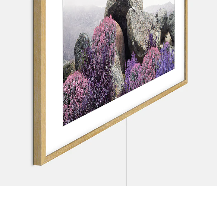 The Frame which is hung on the wall with Slim-fit Wall Mount shows barely visible gap between TV and wall, as well as transparent One Invisible Connection wire.