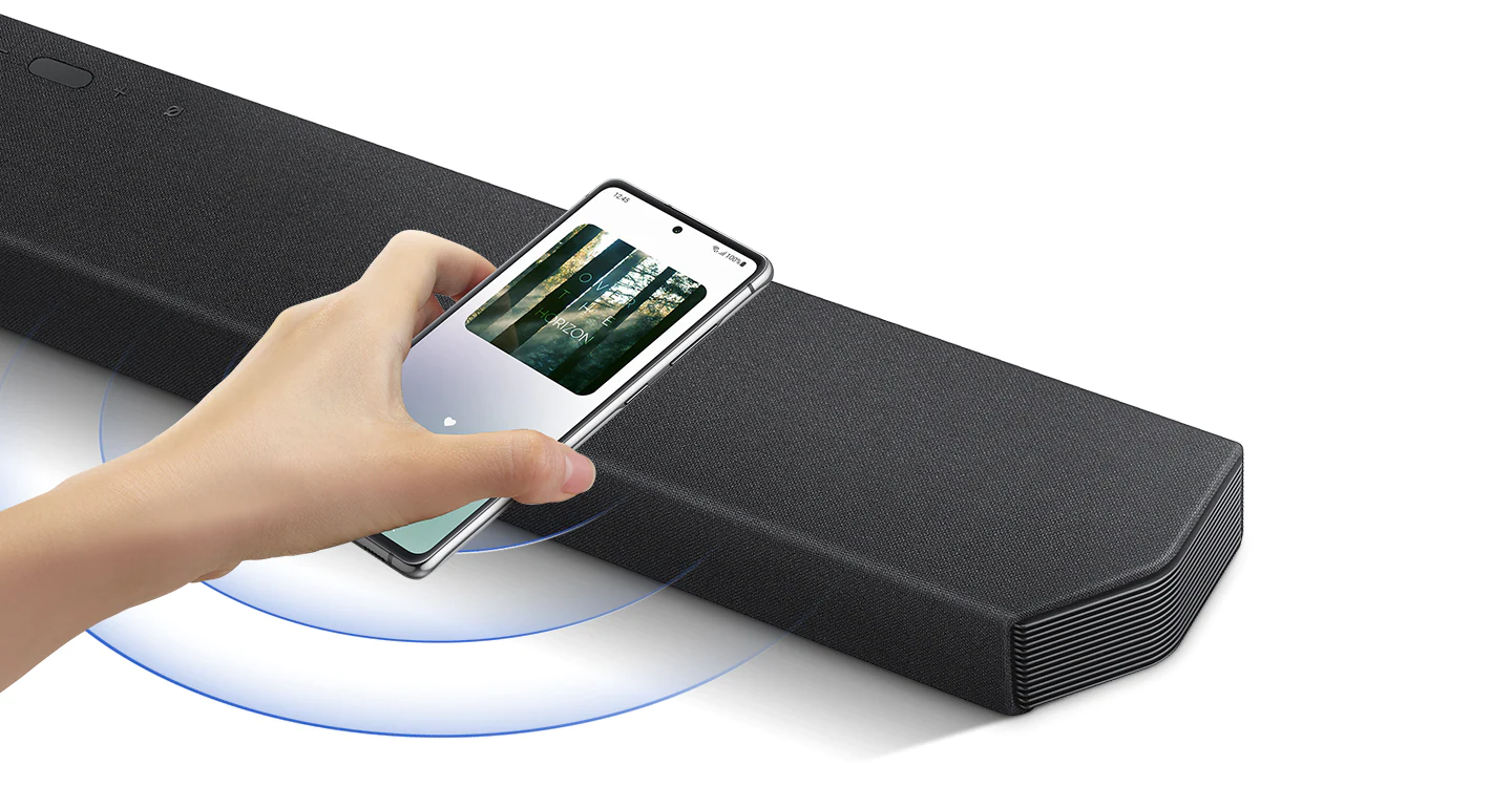 A hand taps a smartphone with the Samsung music app on-screen on the soundbar and the soundbar instantly plays music, showing how easy it is to switch from smartphone to soundbar.