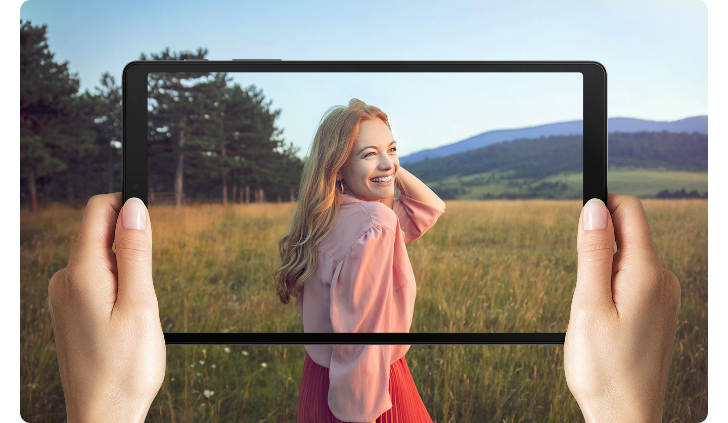 Hands holding Galaxy A7 Lite. Onscreen is a woman standing in a field. The photo goes beyond the boundaries of the screen to represent the wide display.