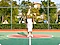 1. A man standing in a basketball court. It is a close crop shot, showing the man and the center of the court.
