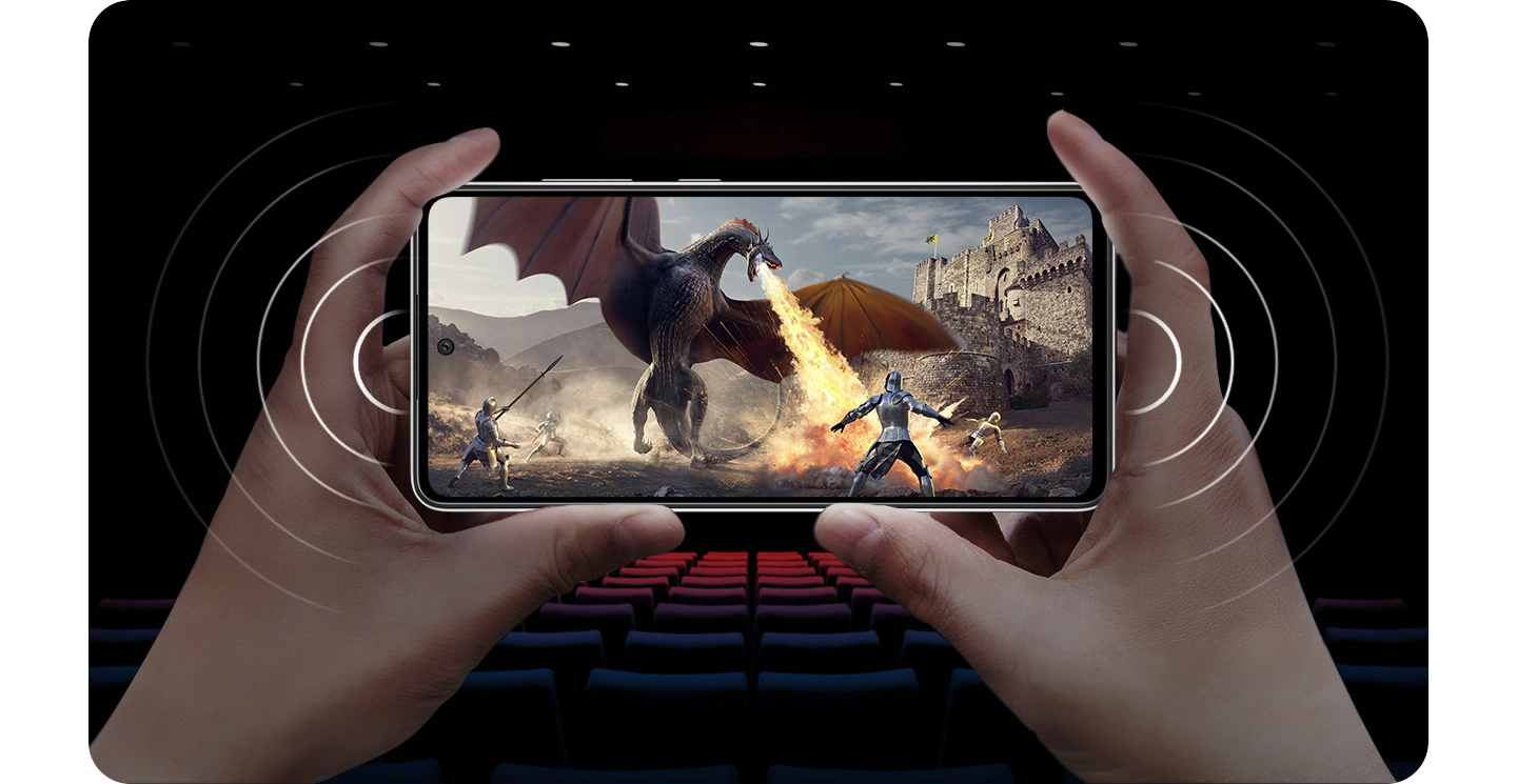 A person holding Galaxy A52 in landscape mode with a scene onscreen of a knight fighting a fire-breathing dragon, and soundwaves coming from either side of the phone to demonstrate stereo speakers.