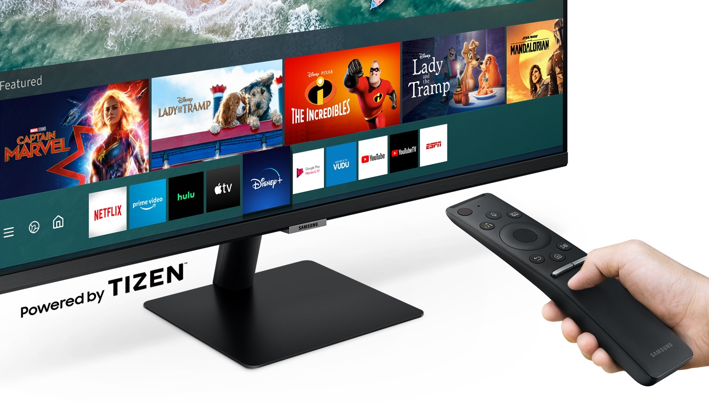 Entertainment apps are displayed on the monitor. A person flips through apps with the monitor's remote control.
