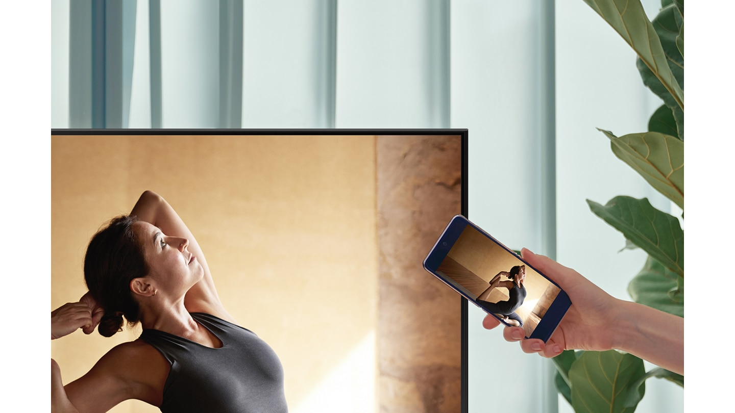 A user taps their smartphone against their AU8000 TV to mirror their ballerina contents to a bigger screen for more comfort.