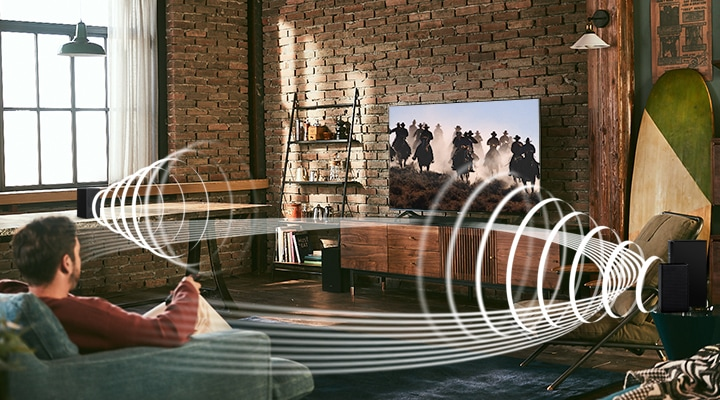 A man enjoys racing content on his TV. Soundwave graphics are playing from Samsung Wireless Rear Speaker Kit and Soundbar, demonstrating Wireless Surround Sound Compatible feature of Samsung soundbar.