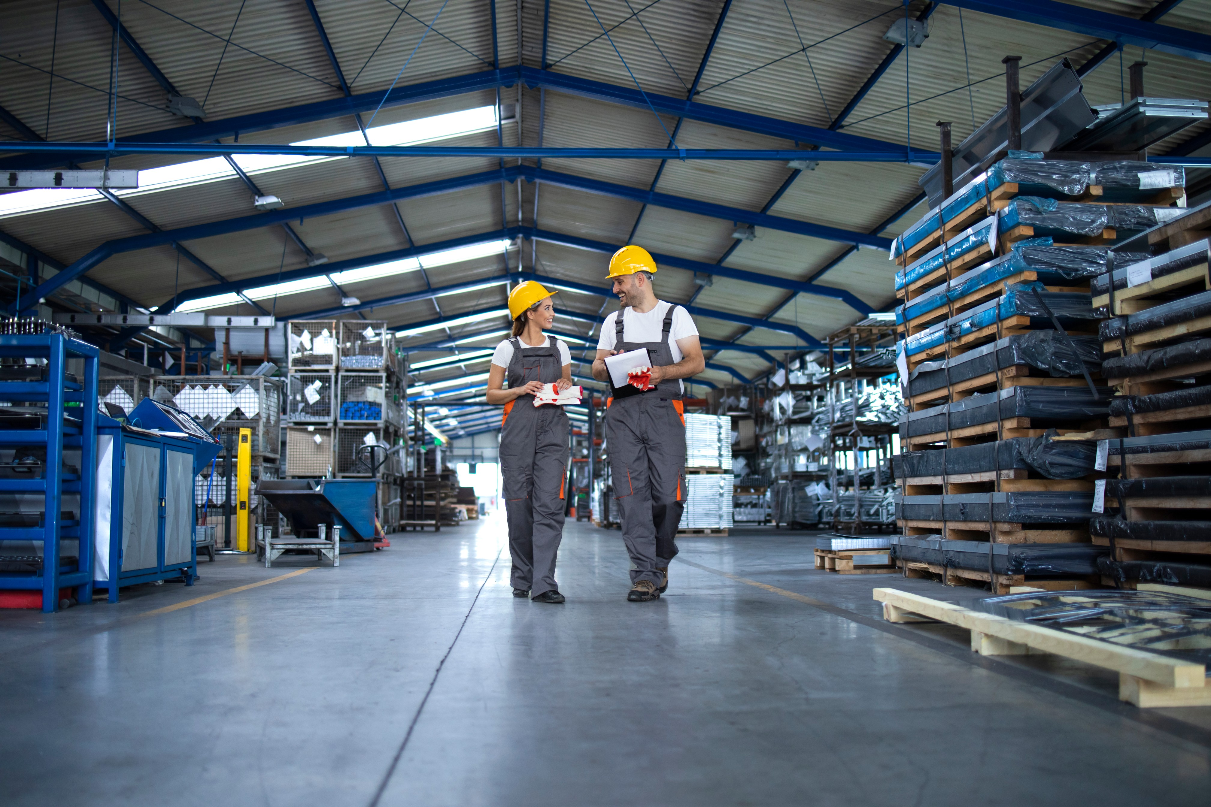 factory-workers-work-wear-yellow-helmets-walking-through-industrial-production-hall-discussing-about-delivery-deadline (1).jpg
