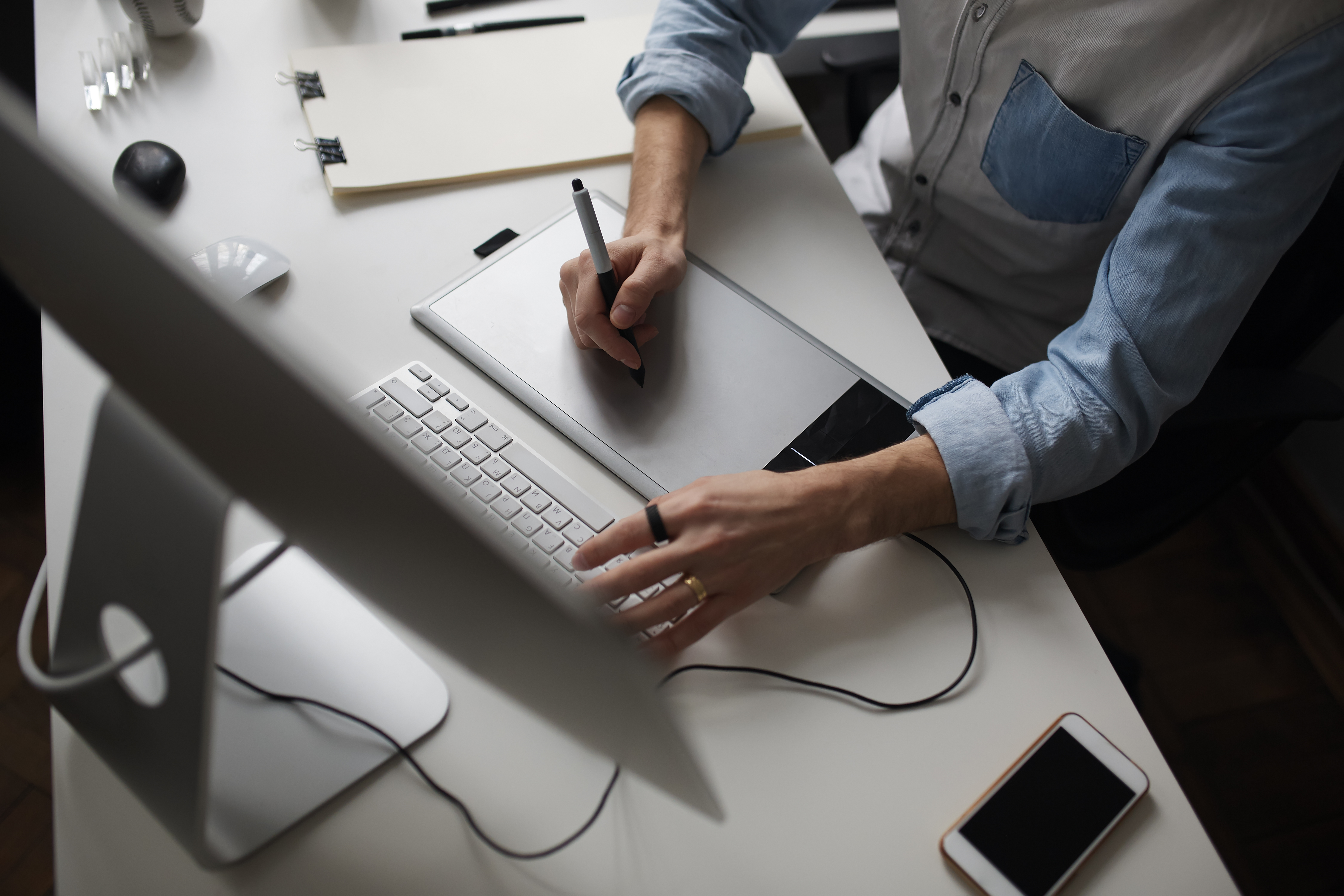 young-male-designer-using-graphics-tablet-while-working-with-com.jpg