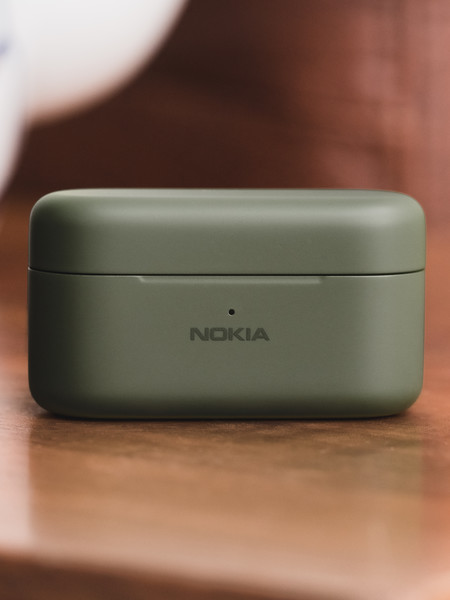 nokia E3200 essential true wireless earphones_Green_on a wooden table with a glass of tea behind