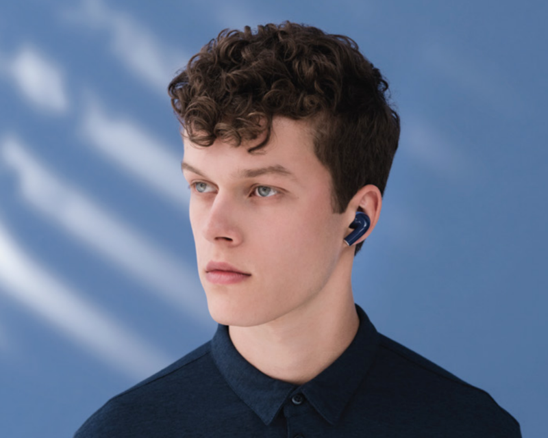 a men listening to music with nokia e3500 essential wireless headphone in front of a blue wall with sunlight