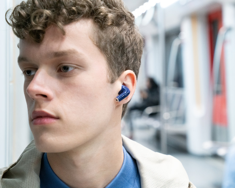 a men listening to music with Nokia e3500 essential truewirelelss earphone on the train