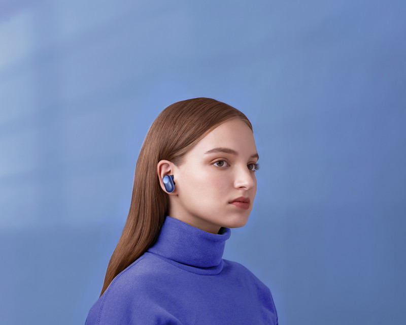 a lady listening to music with a blue color Nokia ANC Professional True Wireless Earphones P3802A in front of a blue wall