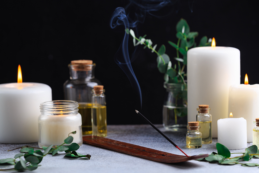 incense-stick-with-smoke-stone-with-white-candles-essential-oils.jpg