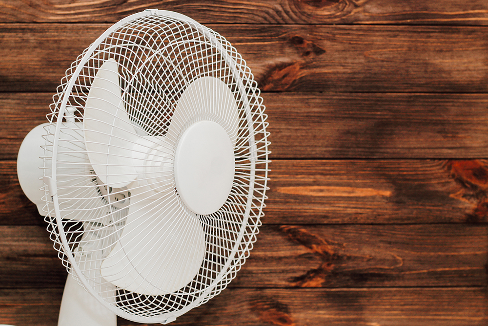 white-fan-with-blades-cooling-room-heat-wooden-background.jpg